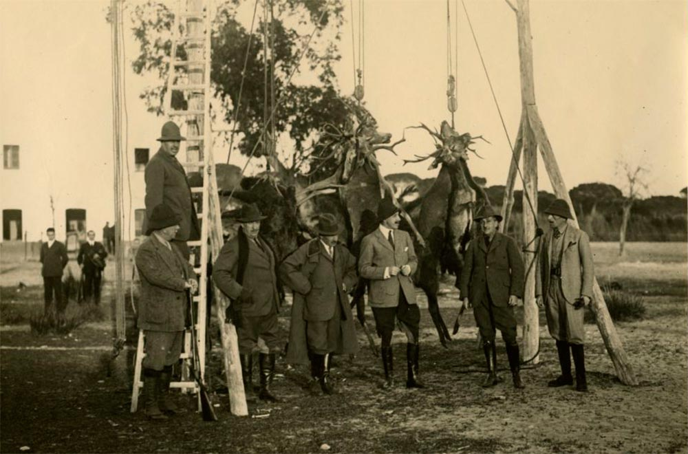 Rey Alfonso XII posando junto al resultado de una cacería