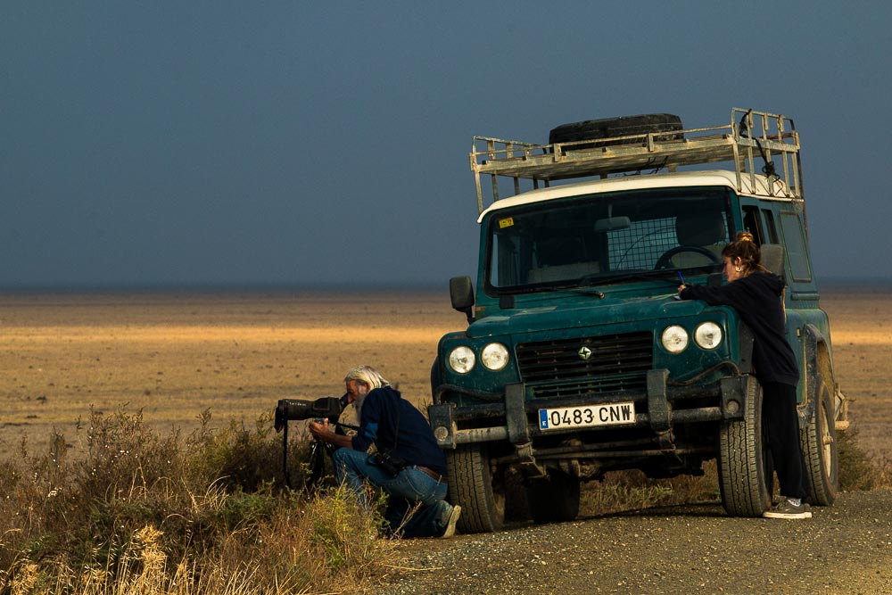 Birdwatcher looking through a telescope next to a land rover