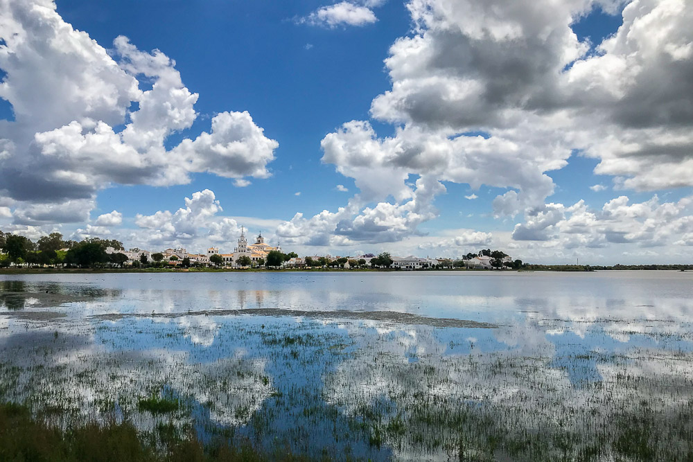 Marshes with white clouds reflected and El Rocio Sanctuary in the background